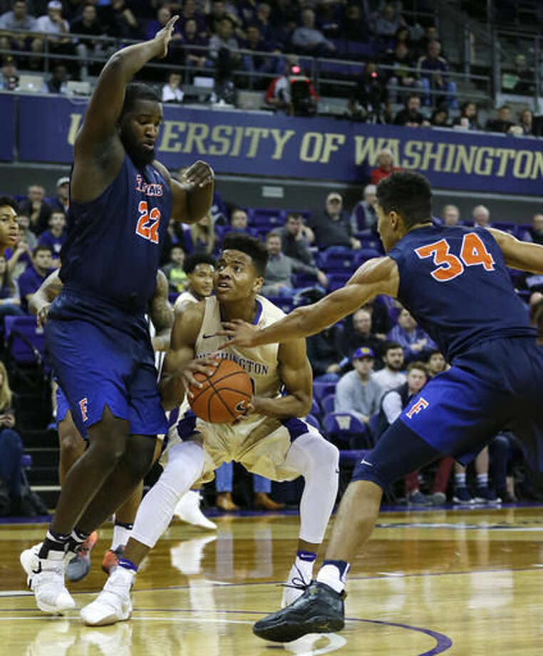 Washington guard Markelle Fultz, center, tries to drive between Cal State Fullerton center Richard Peters, left, and forward Jackson Rowe during the first half of an NCAA college basketball game, Thursday, Nov. 17, 2016, in Seattle. (AP Photo/Ted S. Warren)