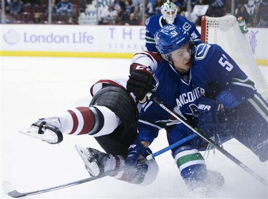 Vancouver Canucks defenseman Troy Stecher (51) collides with Arizona Coyotes right wing Brad Richardson (15) during the first period of an NHL hockey game Thursday, Nov. 17, 2016, in Vancouver, British Columbia. (Jonathan Hayward/The Canadian Press via AP)