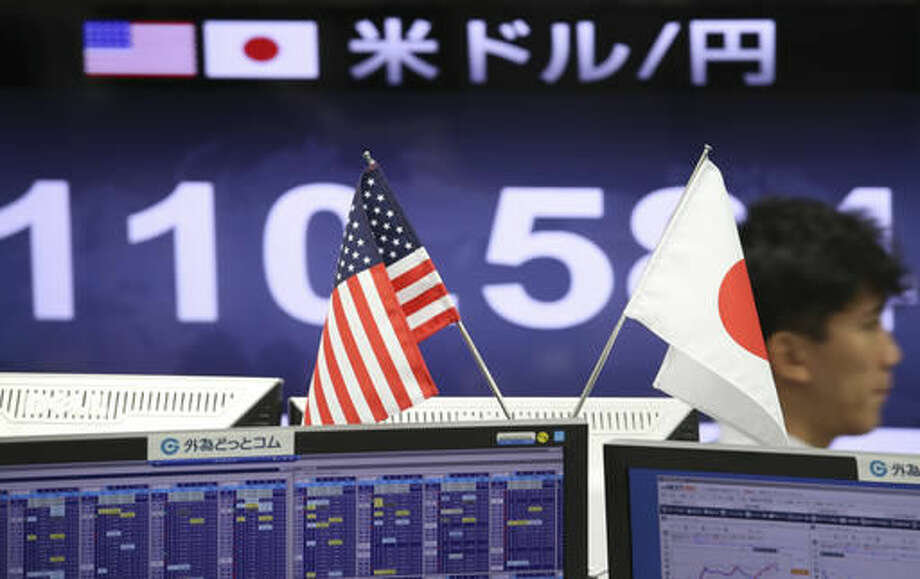 A money trader works at a foreign exchange brokerage in Tokyo, Friday, Nov. 18, 2016. Japanese shares rose Friday on the yen's weakness while other Asian benchmarks wobbled after Fed chair Janet Yellen signaled that policymakers plan to raise interest rates soon. (AP Photo/Koji Sasahara)