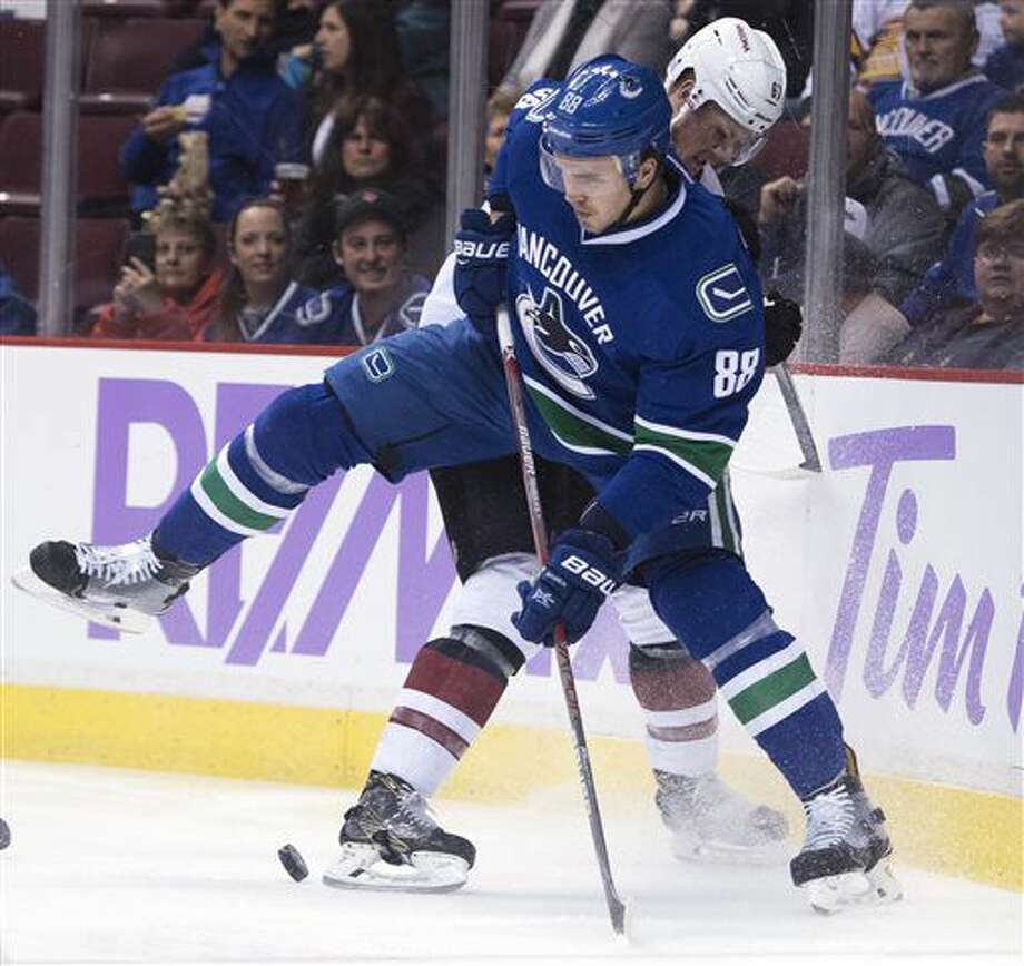 Vancouver Canucks defenseman Nikita Tryamkin (88) fights for control of the puck with Arizona Coyotes left wing Lawson Crouse (67) during the first period of an NHL hockey game Thursday, Nov. 17, 2016, in Vancouver, British Columbia. (Jonathan Hayward/The Canadian Press via AP)