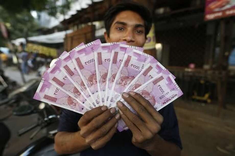 FILE - In this Nov. 11, 2016 file photo, an Indian man displays new currency notes of 2000 Indian rupee in Ahmadabad, India. The sudden withdrawal of 86 percent of India's currency has left cash in short supply, retail sales stumbling and wholesale markets in turmoil. (AP Photo/Ajit Solanki, File)