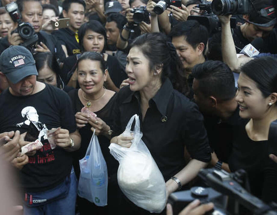 In this Nov. 11, 2016, photo, former Prime Minister Yingluck Shinawatra, center, support farmers by selling their rice to her supporters in Samut Prakan province during the rice price slump in Thailand. Just weeks after Thailand's military government imposed an unprecedented $1 billion fine against an ousted prime minister for her handling of an expensive rice subsidy program, it announced a major assistance plan of its own. It's spending $1.5 billion to help struggling rice farmers, going so far as to dispatch troops into the fields to help farmers harvest the crop. (AP Photo/Sakchai Lalit)