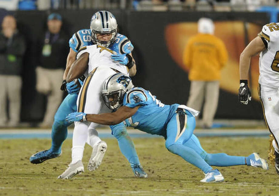Carolina Panthers' Luke Kuechly (59) stops New Orleans Saints' Tim Hightower (34) in the second half of an NFL football game in Charlotte, N.C., Thursday, Nov. 17, 2016. Kuechly was injured on the play. (AP Photo/Mike McCarn)
