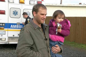 In this image taken from video by KIRO7 photographer Jay Johnson, Jason McAlister holds his daughter at a store Thursday, Nov. 17, 2016, in Matlock, Wash., after they were found safe -- along with McAlister's wife and another of their four children -- earlier Thursday in rural Mason County in Washington state. The couple and the two children were reported missing Tuesday, Nov. 15, 2016, after they went for a drive and failed to pick up their older children after school, authorities said. (@JayOlyKIRO7/KIRO7.com via AP)