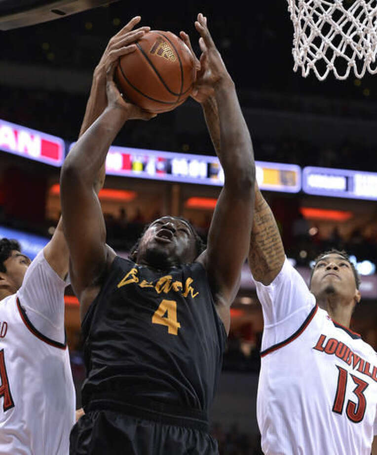 Long Beach State's Temidayo Yussuf (4) attempts a shot between the defense of Louisville's Quentin Snider (4) and Ray Spalding (13) during the first half of an NCAA college basketball game, Thursday, Nov 17, 2016, in Louisville, Ky. (AP Photo/Timothy D. Easley)