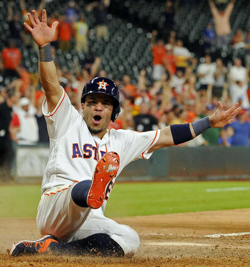 FILE - In this Aug. 1, 2016, file photo, Houston Astros' Jose Altuve scores the winning run on Carlos Correa's single in the 14th inning of a baseball game against the Toronto Blue Jays, in Houston. Altuve, Mike Trout and, Mookie Betts are the finalists for the American League Most Valuable Player award. (AP Photo/Eric Christian Smith, File)
