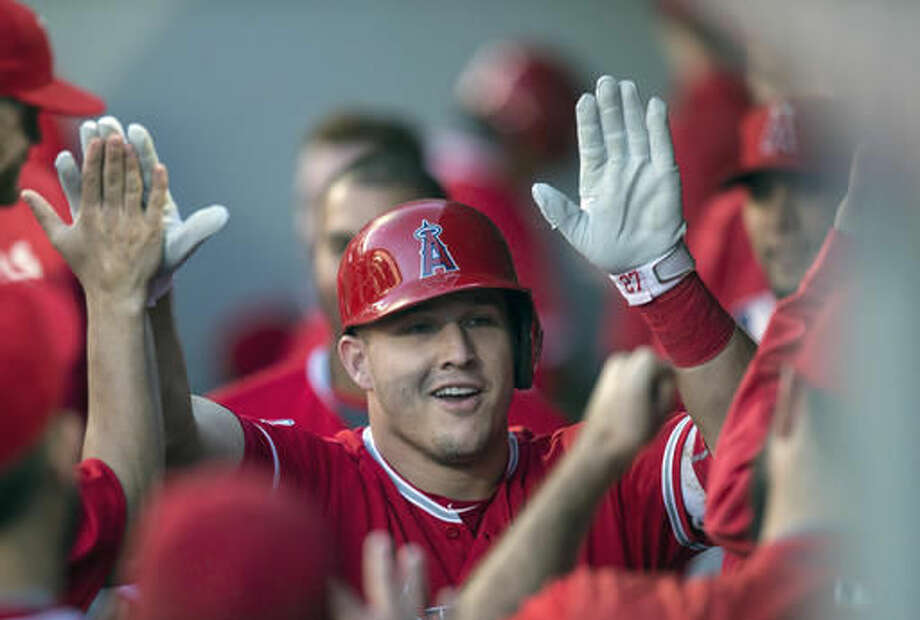 FILE - In this Sept. 3, 2016, file photo, Los Angeles Angels' Mike Trout is congratulated by teammates after hitting a solo home run off Seattle Mariners starter Taijuan Walker during the first inning of a baseball game, in Seattle. Trout, Mookie Betts and Jose Altuve are the finalists for the American League Most Valuable Player award.(AP Photo/Stephen Brashear, File)