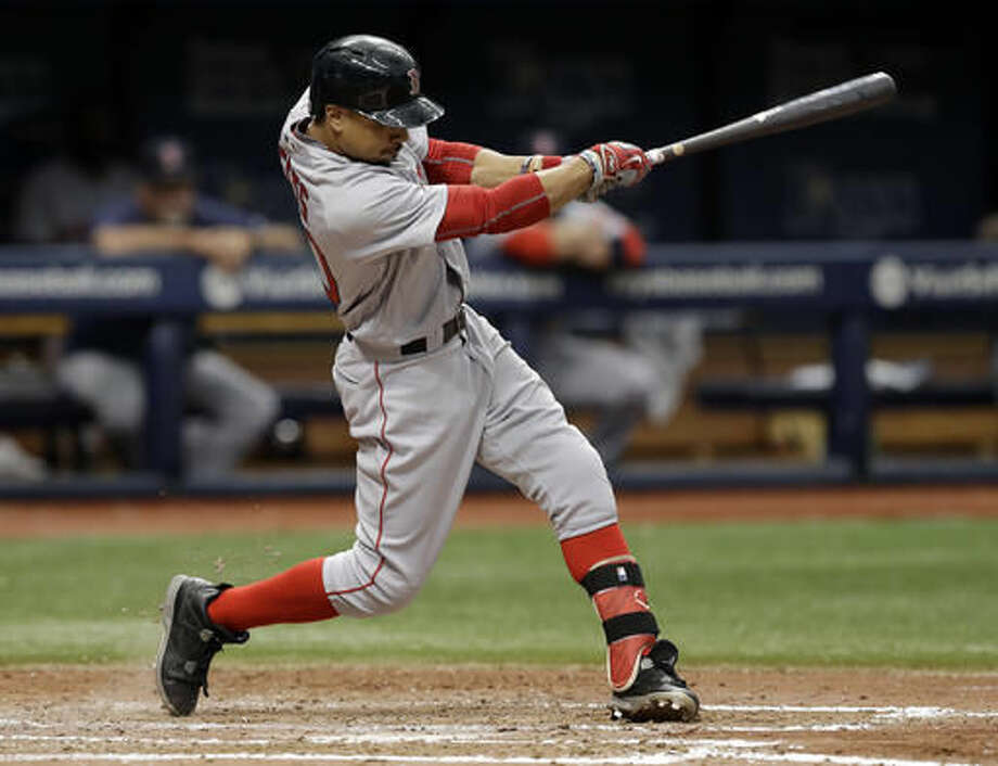 FILE - In this Aug. 25, 2016, file photo, Boston Red Sox's Mookie Betts hits an RBI sacrifice fly off Tampa Bay Rays starting pitcher Jake Odorizzi during the sixth inning of a baseball game, in St. Petersburg, Fla. Betts, Mike Trout and Jose Altuve are the finalists for the American League Most Valuable Player award. (AP Photo/Chris O'Meara, File)