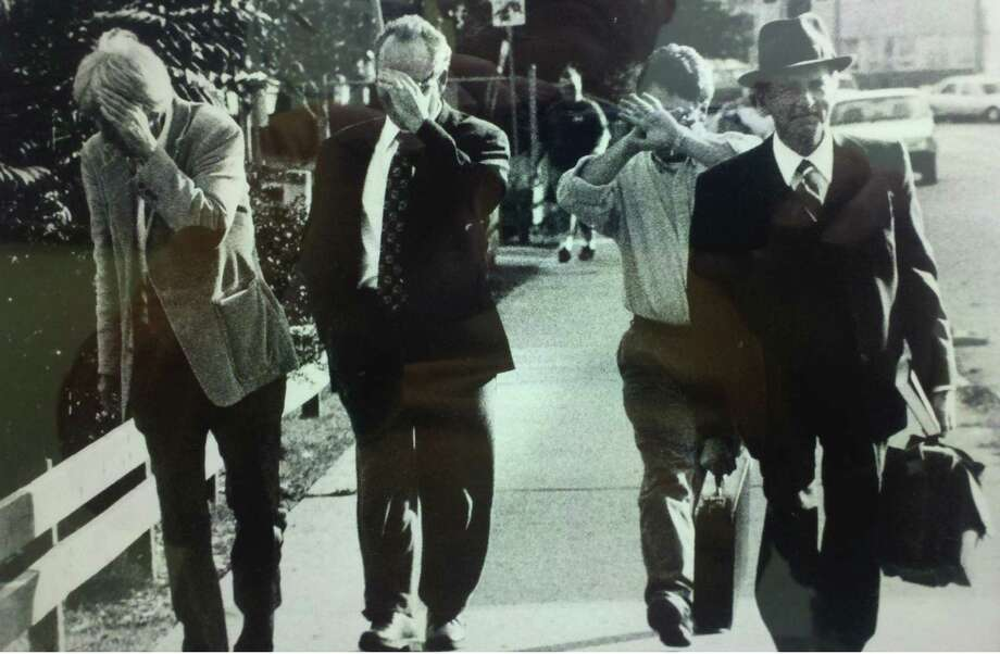 In this photo from the late 1990s, Marv Cermak, left; of the Times Union, and Matthew Roy and Morgan Lyle of the Daily Gazette shield their faces in jest as they walk behind Schenectady City Corporation Counsel Michael Brockbank. The trio pretended to be Brockbank's clients shielding themselves from the media. A framed copy of the photo, taken by Daily Gazette photographer Marc Schulz, sits on Cermak's desk to this day. (Archive photo) Photo: Marc Schultz