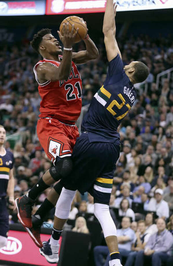 Chicago Bulls forward Jimmy Butler, left, shoots the ball over Utah Jazz center Rudy Gobert, right, during the first half at an NBA basketball game on Thursday, Nov. 17, 2016, in Salt Lake City. (AP Photo/George Frey)