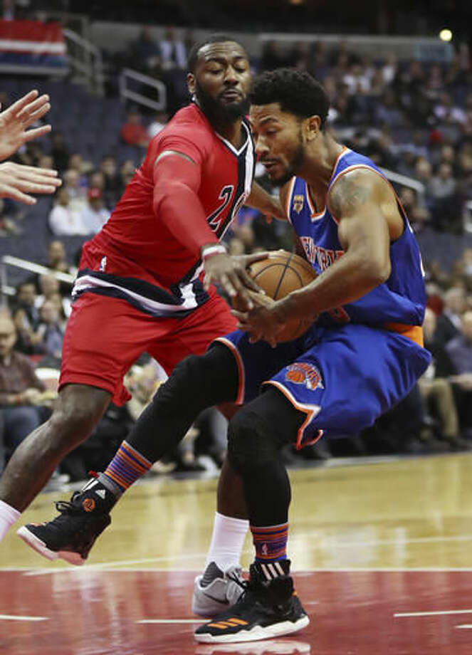 Washington Wizards guard John Wall (2) tries to steal the ball from New York Knicks guard Derrick Rose (25) as Rose drives under the basket during the first half of an NBA basketball game in Washington, Thursday, Nov. 17, 2016. (AP Photo/Manuel Balce Ceneta)