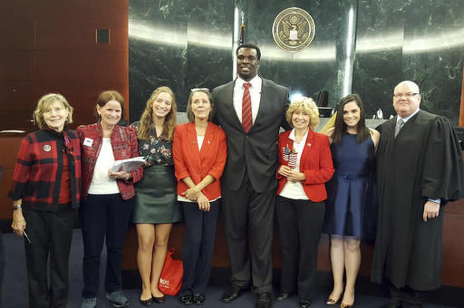 In this photo provided by the U.S. Citizenship and Immigration Services, Buffalo Bills offensive lineman Cyrus Kouandjio is flanked by staff members of the U.S. District Court, Judge Michael J. Roemer, right, and Kouandjio's wife Elizabeth, second from right, after Kouandjio became an American citizen, Thursday Nov. 17, 2016, during a ceremony in U.S. District Court in Buffalo, N.Y. Kouandjio was born in Cameroon and came to the United States with his parents, who settled in Maryland. (U.S. Citizenship and Immigration Services/Anita Moore via AP)