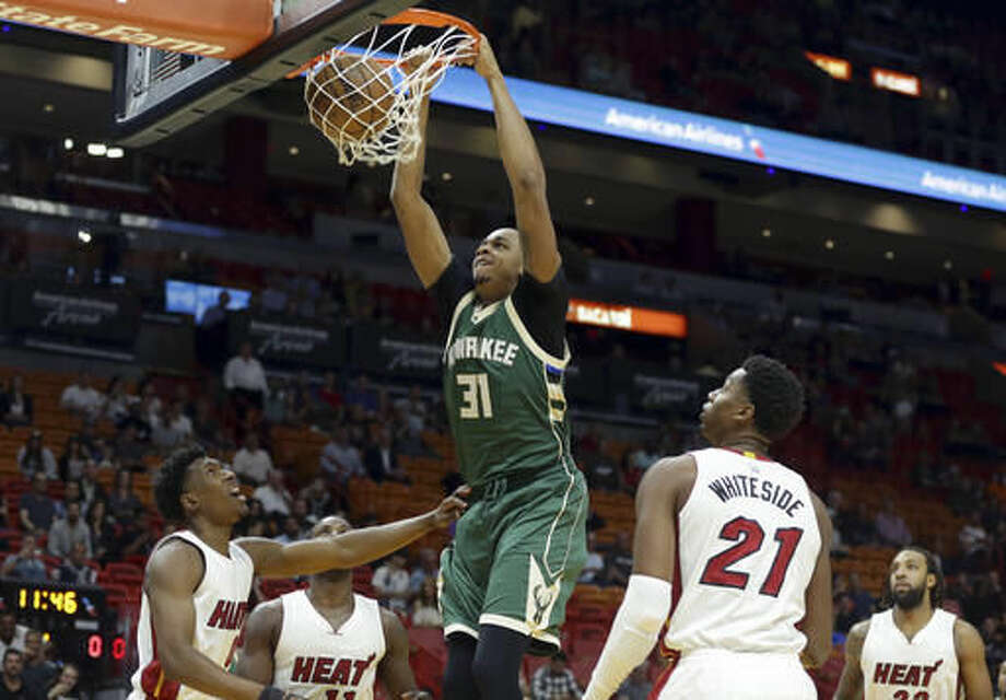 Milwaukee Bucks forward John Henson (31) dunks betweenMiami Heat guard Josh Richardson, left, and center Hassan Whiteside (21) during the first half of an NBA basketball game, Thursday, Nov. 17, 2016, in Miami. (AP Photo/Lynne Sladky)