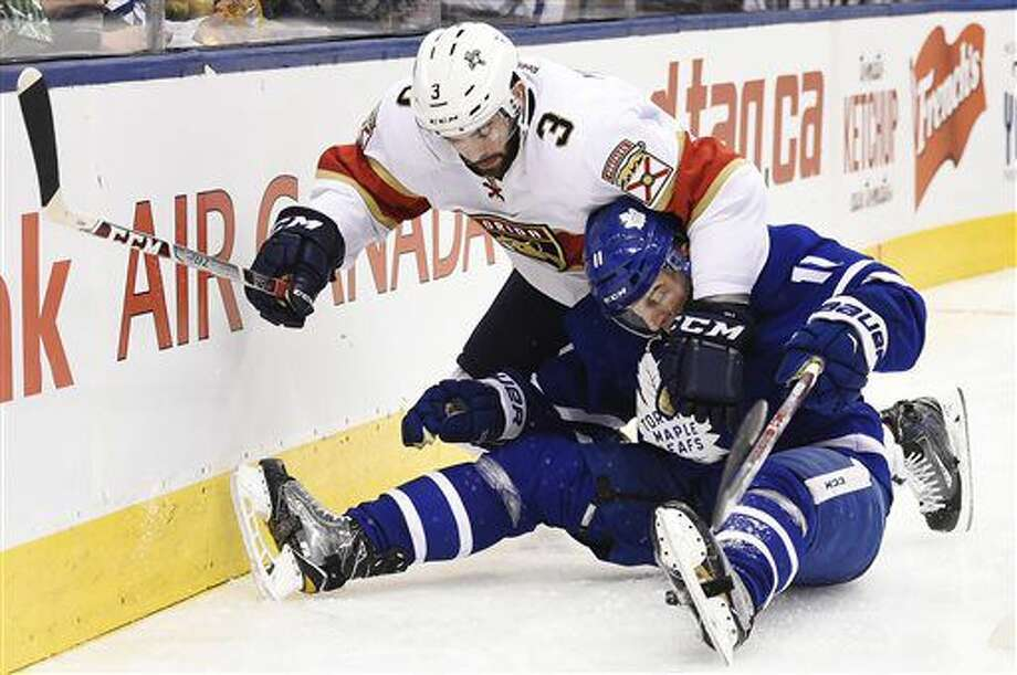 Florida Panthers defenseman Keith Yandle (3) and Toronto Maple Leafs centrerZach Hyman (11) become entangled during second-period NHL hockey game action in Toronto, Thursday, Nov. 17, 2016. (Nathan Denette/The Canadian Press via AP)