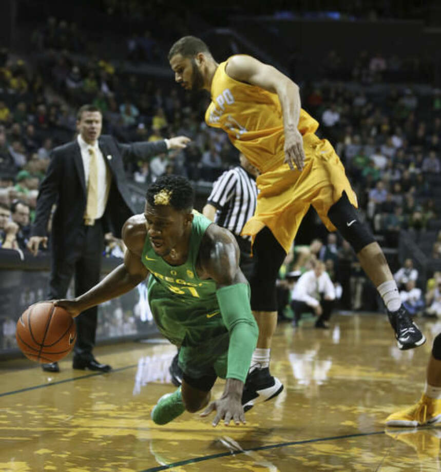 Oregon's Dylan Ennis, center, dives for the ball as Valparaiso head coach Matt Lottich, left, looks on and Valparaiso's Shane Hammink covers, right, during the first half of an NCAA college basketball game Thursday, Nov. 17, 2016, in Eugene, Ore. (AP Photo/Chris Pietsch)