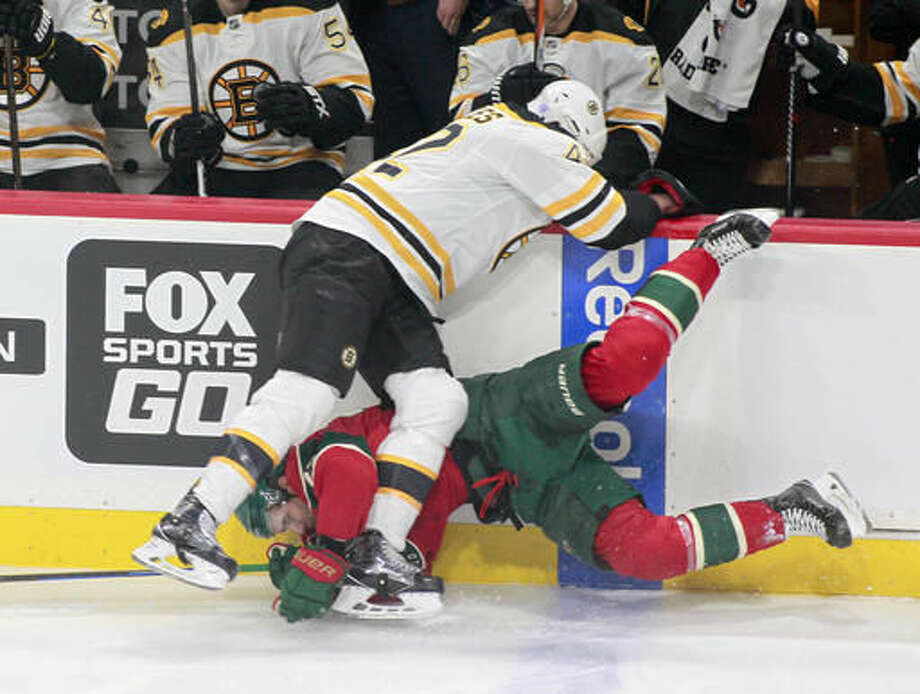 Minnesota Wild right wing Nino Niederreiter, of Switzerland (22) is checked hard into the boards by Boston Bruins right wing David Backes (42) during the first period of an NHL hockey game, Thursday, Nov. 17, 2016, in St. Paul, Minn. (AP Photo/Paul Battaglia)