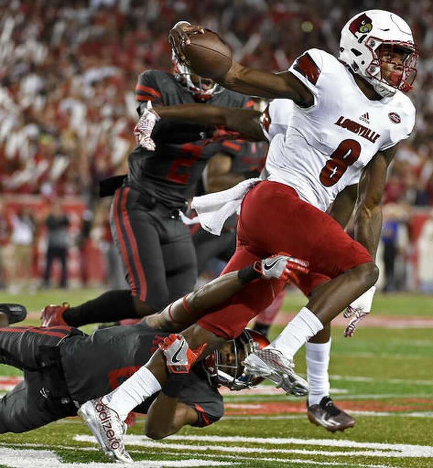 Louisville quarterback Lamar Jackson (8) is tackled by Houston cornerback Howard Wilson (6) during the first half of an NCAA college football game, Thursday, Nov. 17, 2016, in Houston. (AP Photo/Eric Christian Smith)