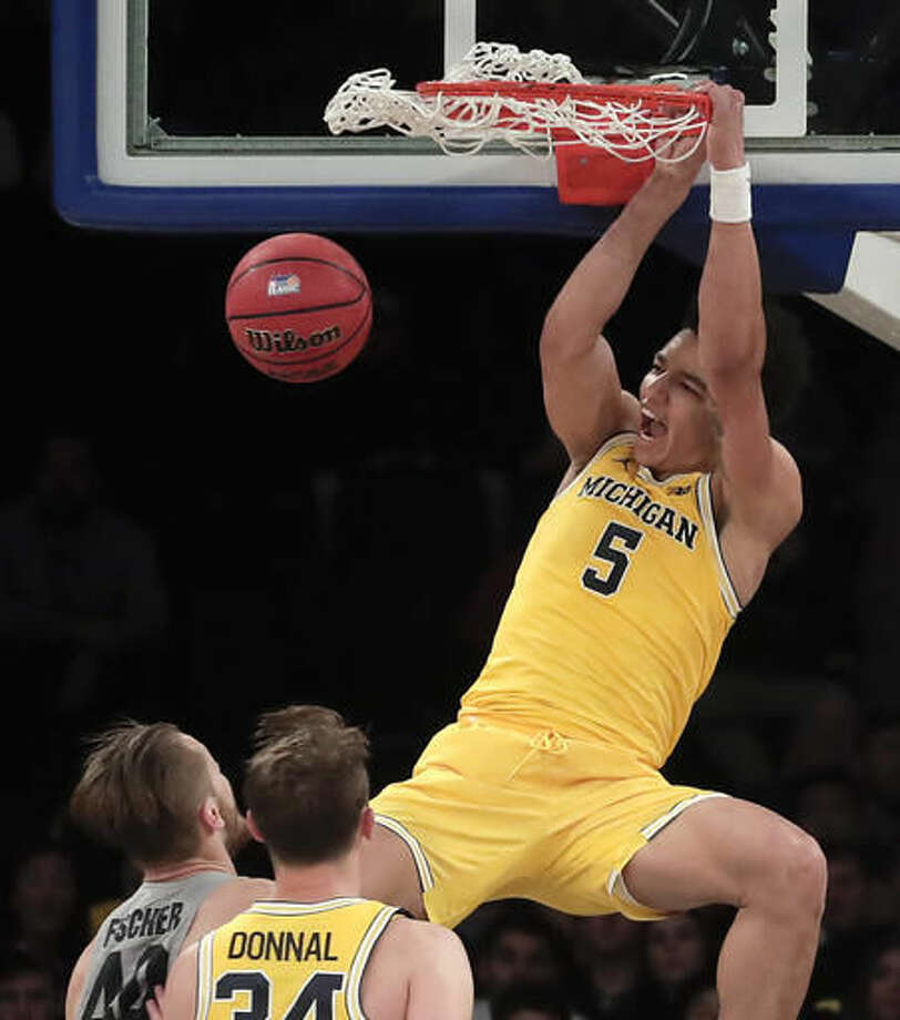 Michigan forward D.J. Wilson (5) dunks against Marquette in the second half of an NCAA college basketball game, Thursday, Nov. 17, 2016, in New York. (AP Photo/Julie Jacobson)