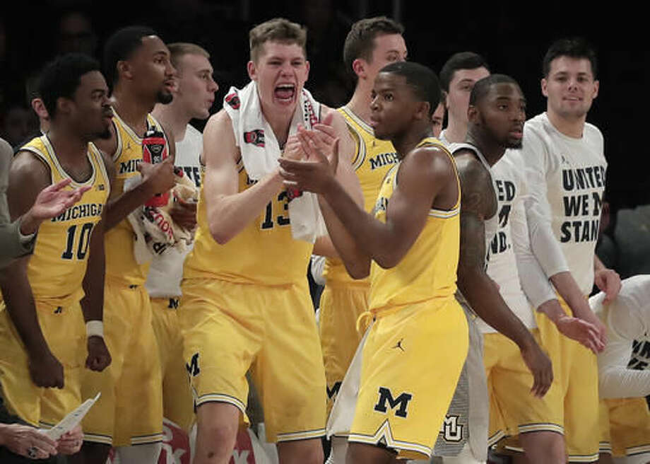 Michigan guard Xavier Simpson, center, reacts, along with his bench, to a turnover by Marquette in the first half of an NCAA college basketball game, Thursday, Nov. 17, 2016, in New York. (AP Photo/Julie Jacobson)