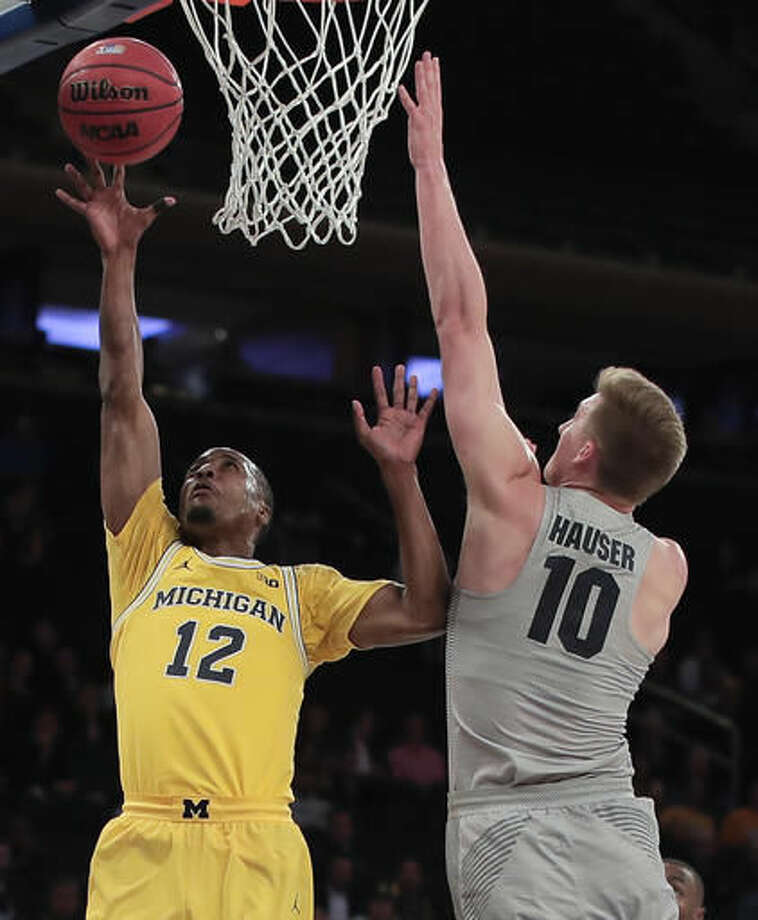 Michigan guard Muhammad-Ali Abdur-Rahkman (12) shoots against Marquette guard Sam Hauser (10) in the first half of an NCAA college basketball game, Thursday, Nov. 17, 2016, in New York. (AP Photo/Julie Jacobson)