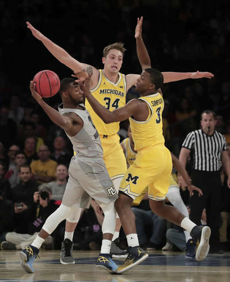 Marquette guard Traci Carter (21) looks to pass the ball against Michigan guard Xavier Simpson (3) and forward Mark Donnal (34) in the first half of an NCAA college basketball game, Thursday, Nov. 17, 2016, in New York. (AP Photo/Julie Jacobson)