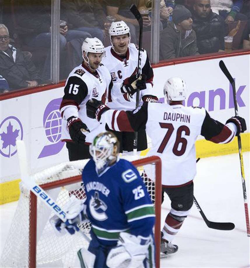 Arizona Coyotes right wing Brad Richardson (15) celebrates his goal with teammates Shane Doan (19) and Laurent Dauphin (76) as Vancouver Canucks goalie Jacob Markstrom (25) stands in front of the net during the second period of an NHL hockey game Thursday, Nov. 17, 2016, in Vancouver, British Columbia. (Jonathan Hayward/The Canadian Press via AP)