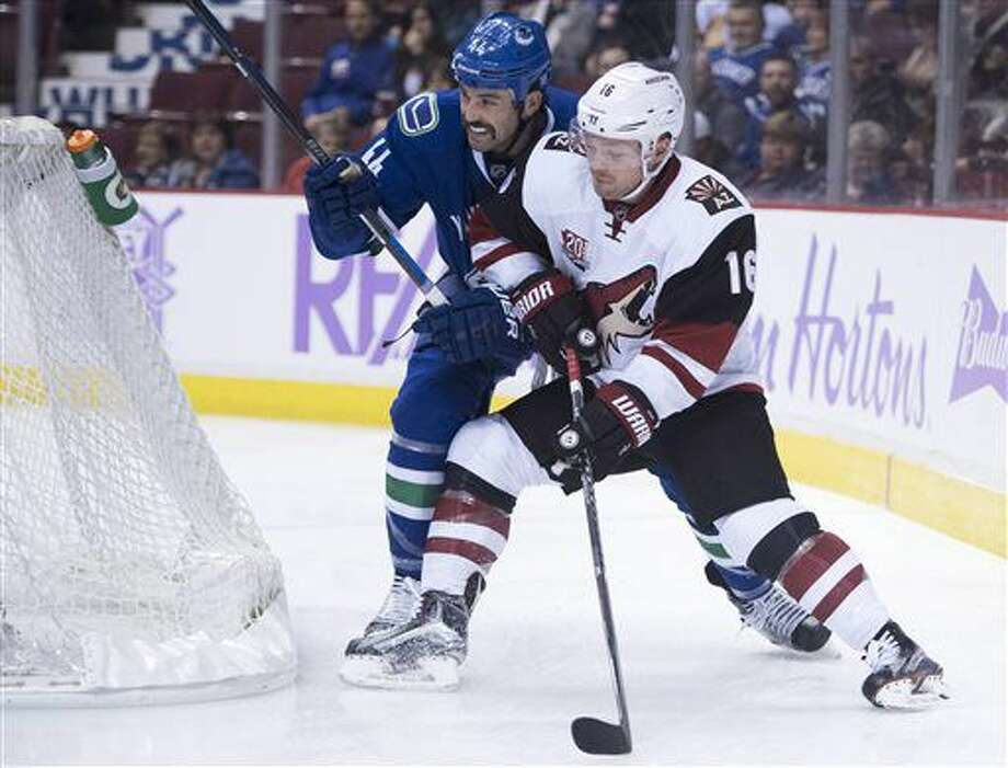 Vancouver Canucks defenseman Erik Gudbranson (44) chases Arizona Coyotes left wing Max Domi (16) behind the net during the first period of an NHL hockey game Thursday, Nov. 17, 2016, in Vancouver, British Columbia. (Jonathan Hayward/The Canadian Press via AP)