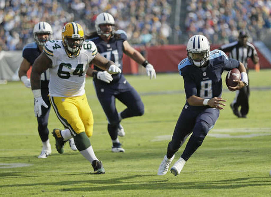 FILE - In this Nov. 13, 2016, file photo, Tennessee Titans quarterback Marcus Mariota (8) scrambles past Green Bay Packers defensive end Mike Pennel (64) in the first half of an NFL football game, in Nashville, Tenn. Mariota has been named the AFC offensive player of the week for his four-TD performance against Green Bay on Sunday. (AP Photo/James Kenney, File)