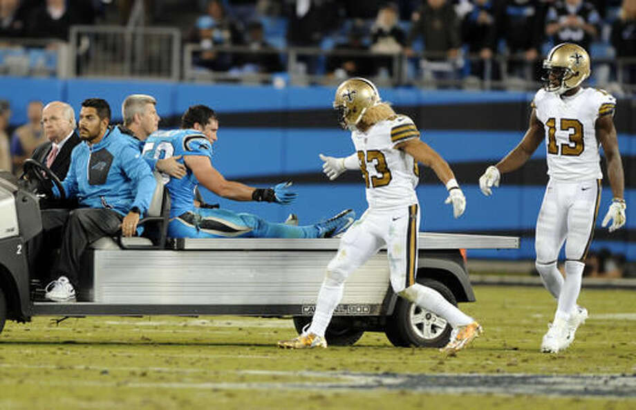 New Orleans Saints' Willie Snead (83) reaches to Carolina Panthers' Luke Kuechly (59) as he is carted off the field in the second half of an NFL football game in Charlotte, N.C., Thursday, Nov. 17, 2016. (AP Photo/Mike McCarn)