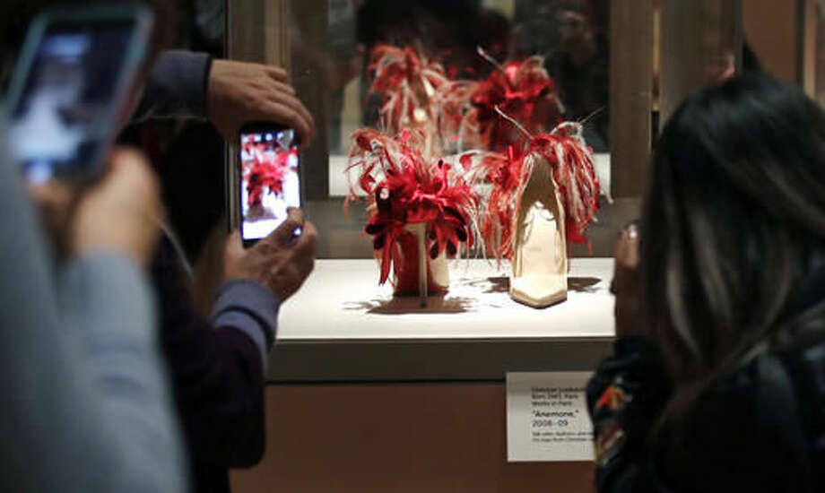 """In this Tuesday, Nov. 15, 2016 photo, guests snap photographs of a pair of high heels, decorated with red frilled details, are displayed at the Peabody Essex Museum in Salem, Mass. From flats to stilettos, what we put on our feet says something about who we are. That's the premise of new exhibition in Massachusetts. """"Shoes: Pleasure and Pain"""" opens Saturday, Nov. 19, 2016, at the Peabody Essex Museum in Salem. (AP Photo/Charles Krupa)"""