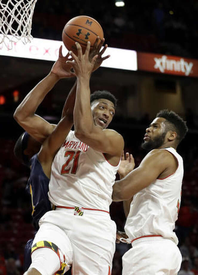 Maryland forward Justin Jackson, center, of Canada, grabs a rebound over teammate Damonte Dodd, right, and St. Mary's of Maryland guard Alie Kondeh in the first half of an NCAA college basketball game, Thursday, Nov. 17, 2016, in College Park, Md. (AP Photo/Patrick Semansky)