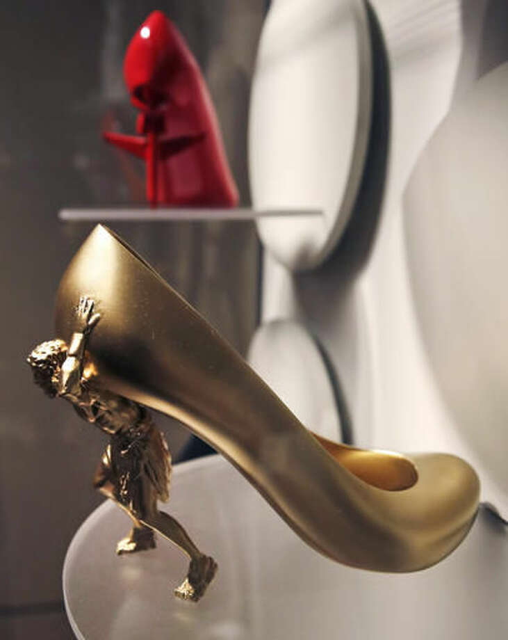 "In this Tuesday, Nov. 15, 2016 photo, a high heel shoe titled ""The Gold Digger"" by designer Sebastian Errazuriz, featuring a figure holding up the upper portion, is displayed at the Peabody Essex Museum in Salem, Mass., From flats to stilettos, what we put on our feet says something about who we are. That's the premise of new exhibition in Massachusetts. ""Shoes: Pleasure and Pain"" opens Saturday, Nov. 19, 2016, at the Peabody Essex Museum in Salem. (AP Photo/Charles Krupa)"
