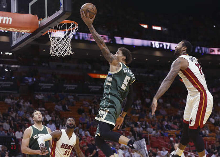 Milwaukee Bucks forward Michael Beasley (9) shoots between Miami Heat forward Willie Reed, second from left, and forward James Johnson, right, during the first half of an NBA basketball game, Thursday, Nov. 17, 2016, in Miami. (AP Photo/Lynne Sladky)