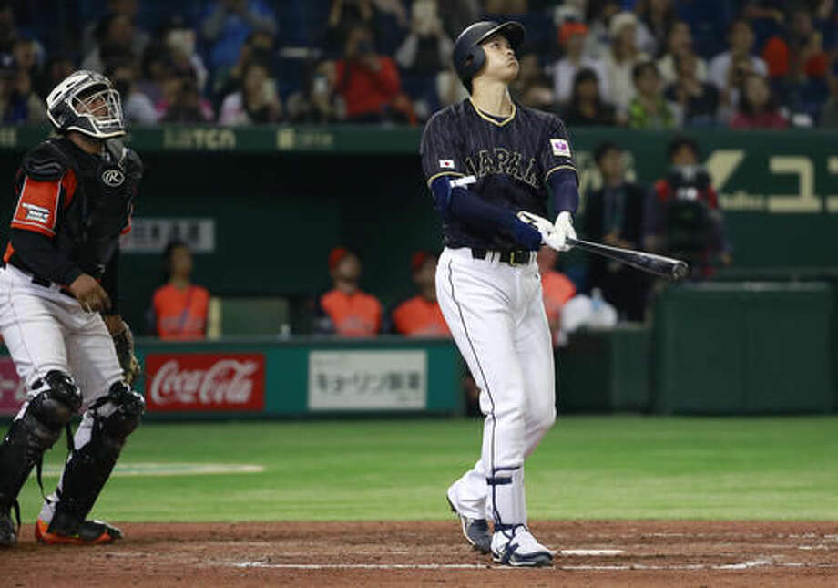 Japan's pinch hitter Shohei Otani watches the flight of his ground-rule double with Netherlands' catcher Dashenko Ricardo in the seventh inning of their international exhibition series baseball game at Tokyo Dome in Tokyo, Sunday, Nov. 13, 2016. (AP Photo/Shizuo Kambayashi)