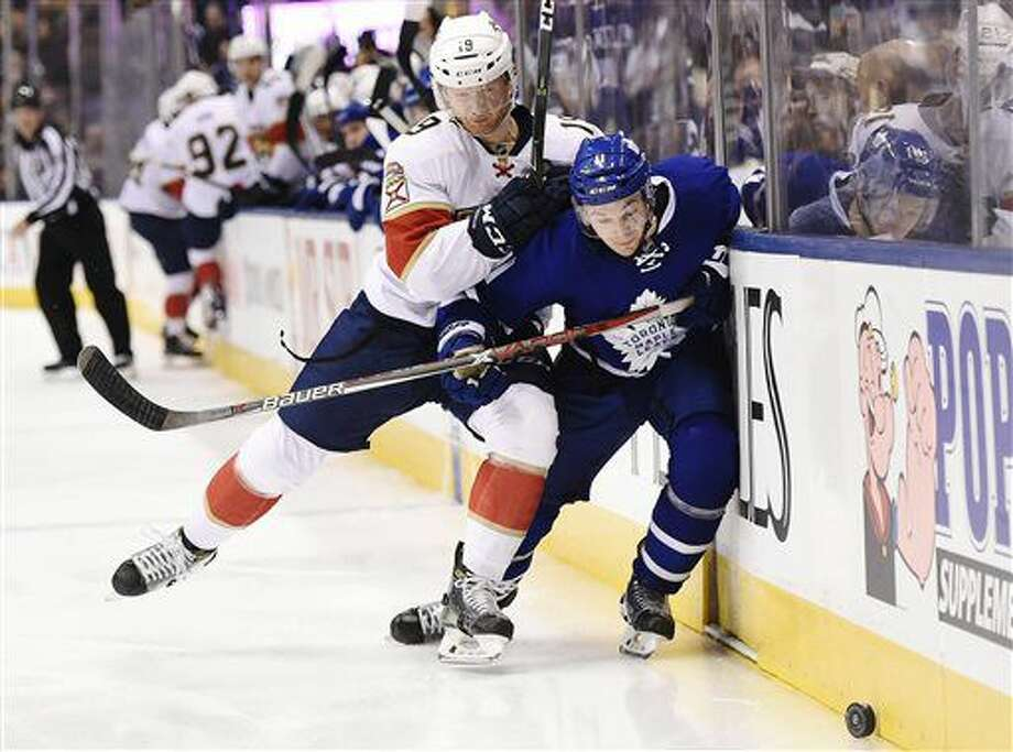 Florida Panthers defenseman Michael Matheson (19) hits Toronto Maple Leafs center Zach Hyman (11) during second-period NHL hockey game action in Toronto, Thursday, Nov. 17, 2016. (Nathan Denette/The Canadian Press via AP)