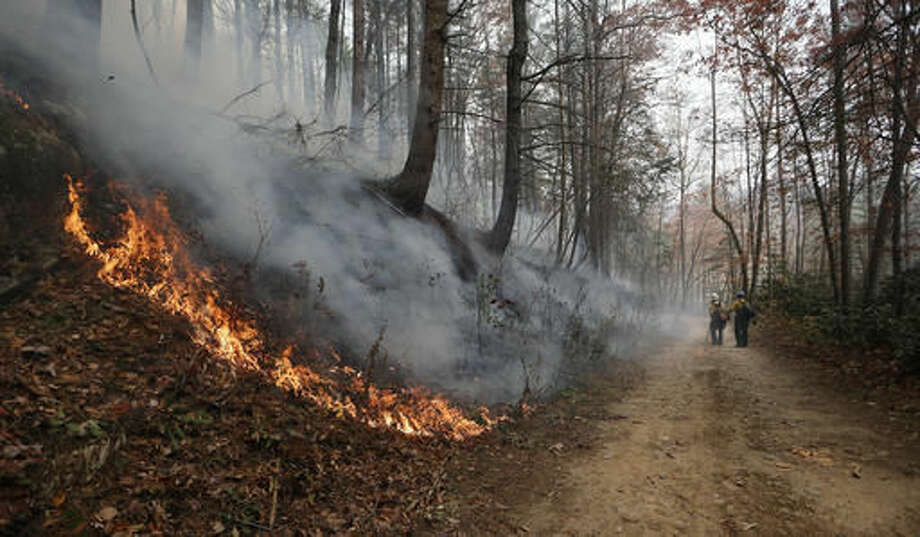 Firefighters walk down a dirt road a wildfire burns a hillside Tuesday, Nov. 15, 2016, in Clayton, Ga. On Tuesday, the Tennessee Valley Authority issued a burn ban on its public lands across Tennessee and in parts of Alabama, Georgia, Kentucky, Mississippi, North Carolina and Virginia. U.S. Forest Service spokesman Adam Rondeau has said the agency is tracking wildfires that have burned a total of 80,000 acres across the South. (AP Photo/John Bazemore)