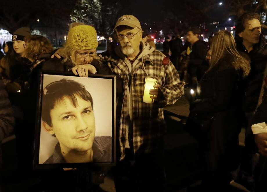 Judy Hough, left, and her husband Brian, center, hold a picture of their son Travis, who died in a warehouse fire, during a vigil at Lake Merritt on Monday, Dec. 5, 2016, in Oakland, Calif. Family members and friends are being notified as firefighters continue a painstaking search for victims of the Oakland warehouse fire. Photo: Marcio Jose Sanchez/AP