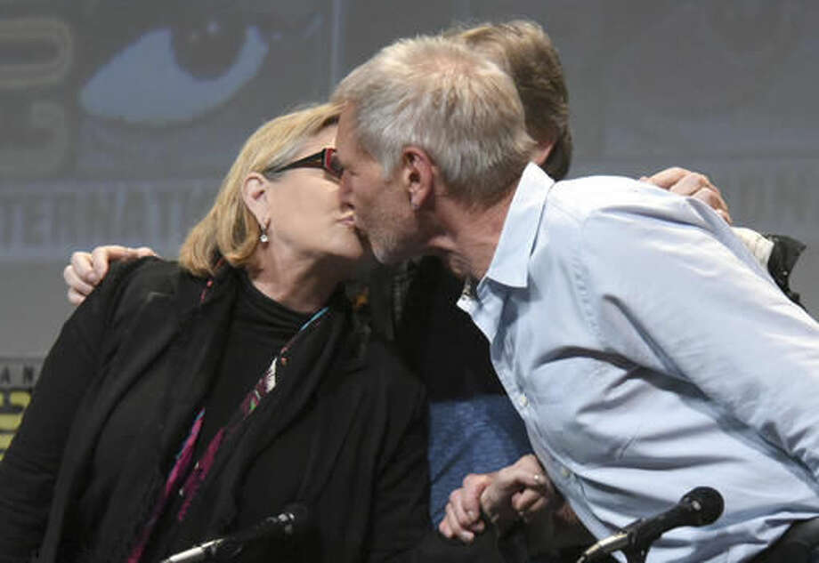 """FILE - In this July 10, 2015, file photo, Carrie Fisher, left, and Harrison Ford kiss at the Lucasfilm's """"Star Wars: The Force Awakens"""" panel on day 2 of Comic-Con International in San Diego, Calif. Fisher revealed in an interview with People magazine published online on Nov. 15, 2016, that she had an affair with Ford during the filming of the 1977 film, """"Star Wars."""" (Photo by Richard Shotwell/Invision/AP, File)"""