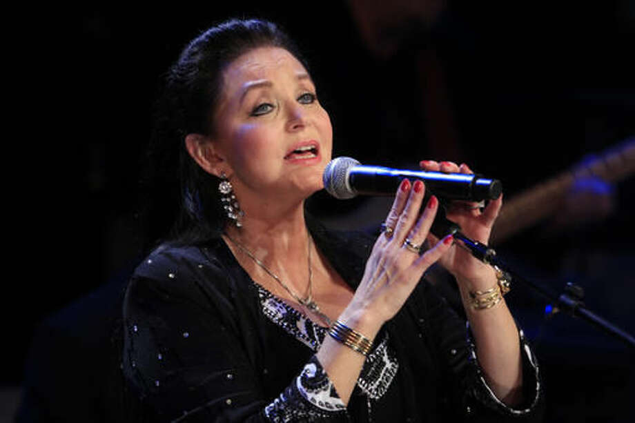 "FILE - In this Oct. 21, 2012 file photo, Crystal Gayle performs at the Country Music Hall of Fame Inductions in Nashville, Tenn. Country star Carrie Underwood had a surprise for Gayle during her performance at the Grand Ole Opry on Tuesday night. After they both finished a duet performance of Gayle's crossover hit, ""Don't It Make My Brown Eyes Blue,"" Underwood invited Gayle to become an official Opry member. (Photo by Wade Payne/Invision/AP, File)"