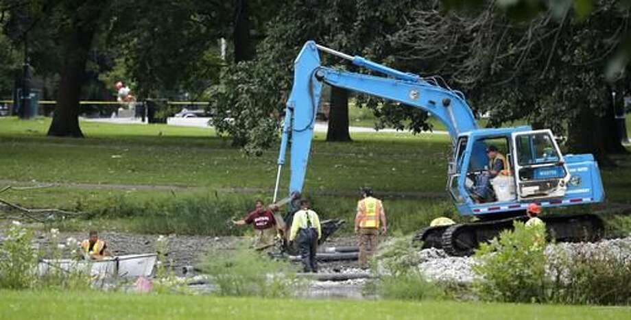 FILE - In this Sept. 10, 2015 file photo, employees from the City of Chicago Water Management office and police department work near the scene in Chicago's Garfield Park lagoon where the dismembered body of a young child was found. Kamel Harris, already in jail in another case, has been charged in the death of a 2-year-old northern Illinois boy whose dismembered remains were found in a park lagoon last year, Chicago police said Tuesday, Nov. 15, 2016. (AP Photo/Charles Rex Arbogast File)