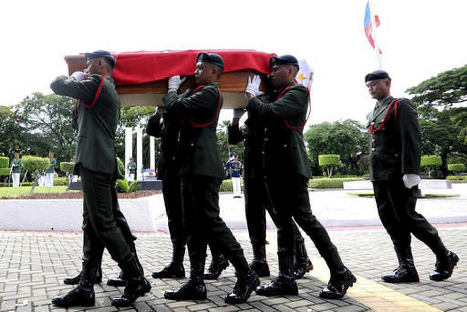 "In this photo provided by the Office of Ilocos Norte Governor Imee Marcos, soldiers carry a flag-draped casket of the late dictator Ferdinand Marcos during a ceremony of his burial at the Heroes' Cemetery in suburban Taguig city, Philippines, Friday, Nov. 18, 2016. Marcos was buried ""like a thief in the night"" Friday at the country's Heroes' Cemetery in a secrecy-shrouded ceremony which opponents said mocked the democratic triumph Filipinos won when a ""people power"" revolt ousted him three decades ago. (Office of Ilocos Norte Governor Imee Marcos via AP)"