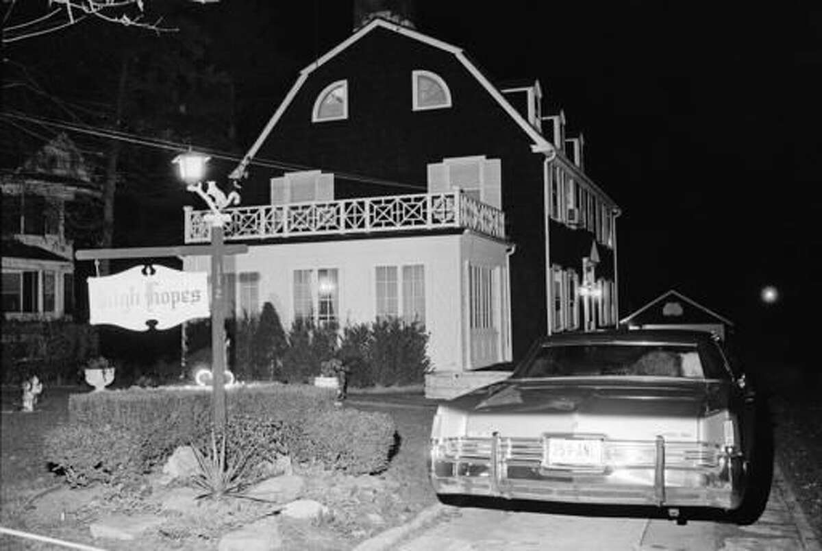 """FILE - In this Nov. 14, 1974 file photo, police and members of the Suffolk County Coroner's Office investigate the murder of six people found shot in Amityville, N.Y. The Long Island home that served as the inspiration for the book """"The Amityville Horror"""" and the subsequent films of the same name is being bought. Newsday reports, Friday, Nov. 18, 2016, the infamous 1927 Dutch Colonial went into contract this week. (AP Photo/Richard Drew, File)"""