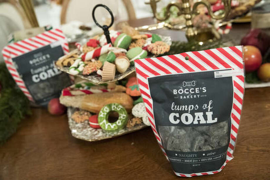 In this Thursday, Nov. 10, 2016 photo Bocce's Bakery Lumps of Coal and other dog treats are on display at the PetSmart holiday collection preview in New York. More than half of dog owners and nearly 40 percent of cat owners buy their pets gifts for Christmas or Hanukkah, according to the American Pet Products Association, an industry trade group. (AP Photo/Mary Altaffer)