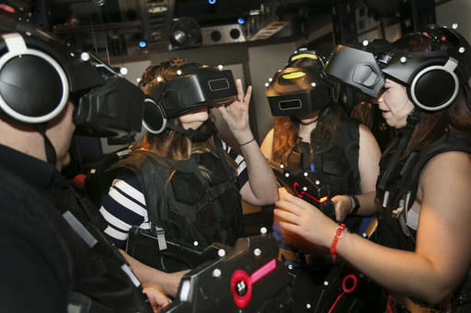 """The Ferrito family dons headgear and other items in preparation to enter a virtual reality experience called """"Ghostbusters: Dimension"""" at Madame Tussauds in New York, Aug. 4, 2016. People who are curious about virtual reality but don't want to plunk down $1,000 or more on hardware are increasingly getting the chance to test out the medium for a price. From roller coaster rides to baseball games, VR can bring a new level of reality or simply detract from it. (AP Photo/Seth Wenig)"""