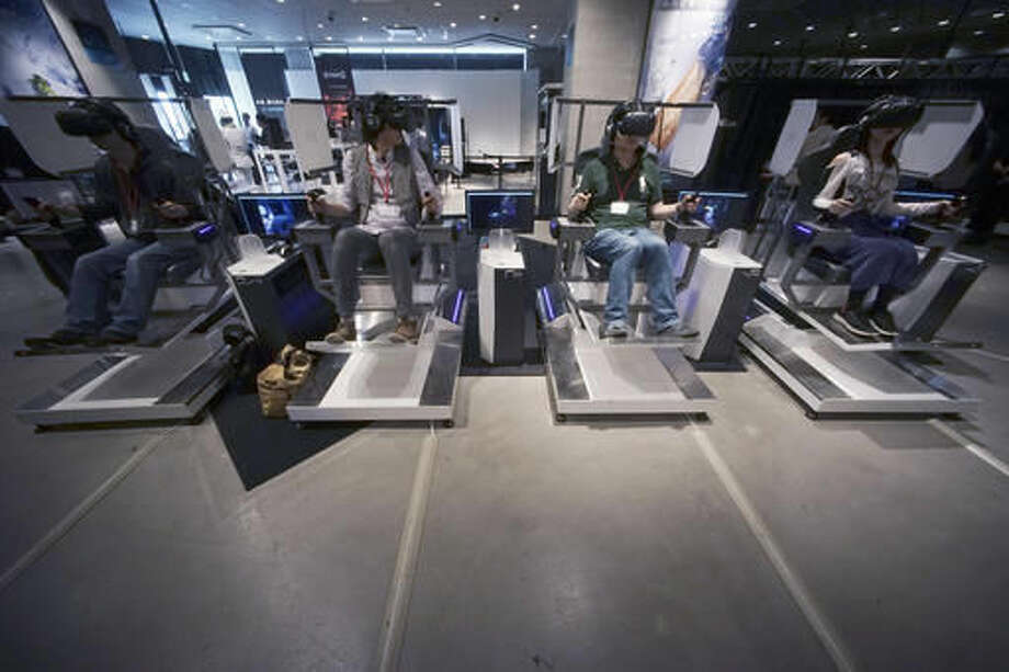 """In this May 31, 2016 photo, visitors, wearing U.S. maker HTC's Vive headsets, operate giant robots as they play battles at the """"VR Zone Project i Can"""" virtual reality experimental entertainment facility in Tokyo. The giant robot is one of eight VR experiences created by game-maker Bandai Namco for HTC's Vive headset. Another entails shooting flying robotic spaceships with a manga-like female character as your co-pilot. (AP Photo/Eugene Hoshiko)"""
