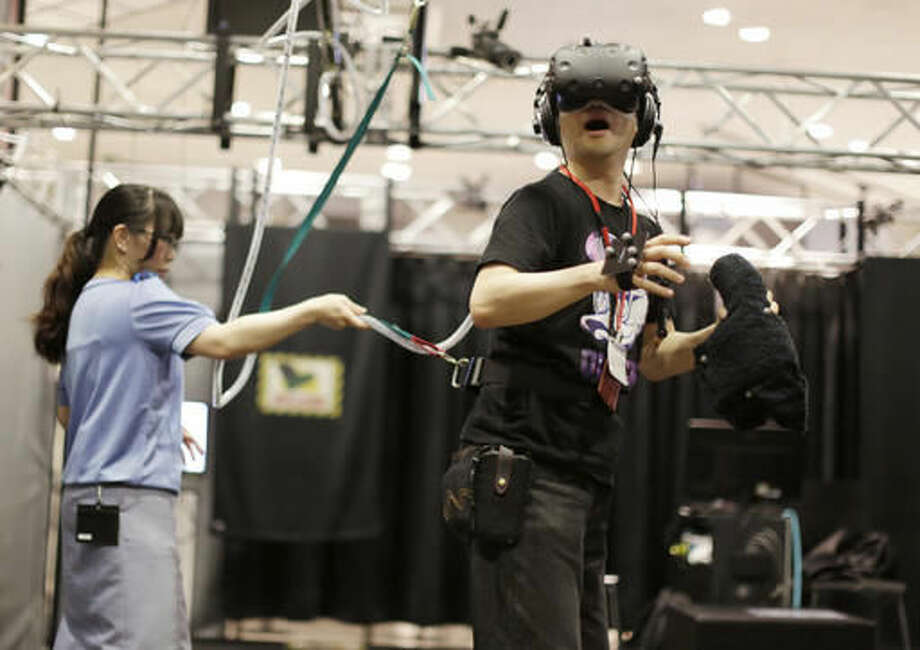 """In this May 31, 2016 photo, a visitor, wearing a U.S. maker HTC's Vive headset, plays """"Fear of Heights Show"""" to rescue a mewling cat perched on a wooden plank that balances from the edge of a skyscraper at the """"VR Zone Project i Can"""" virtual reality experimental entertainment facility in Tokyo. The cat rescue is one of eight VR experiences created by game-maker Bandai Namco for HTC's Vive headset. Another entails shooting flying robotic spaceships with a manga-like female character as your co-pilot. (AP Photo/Eugene Hoshiko)"""