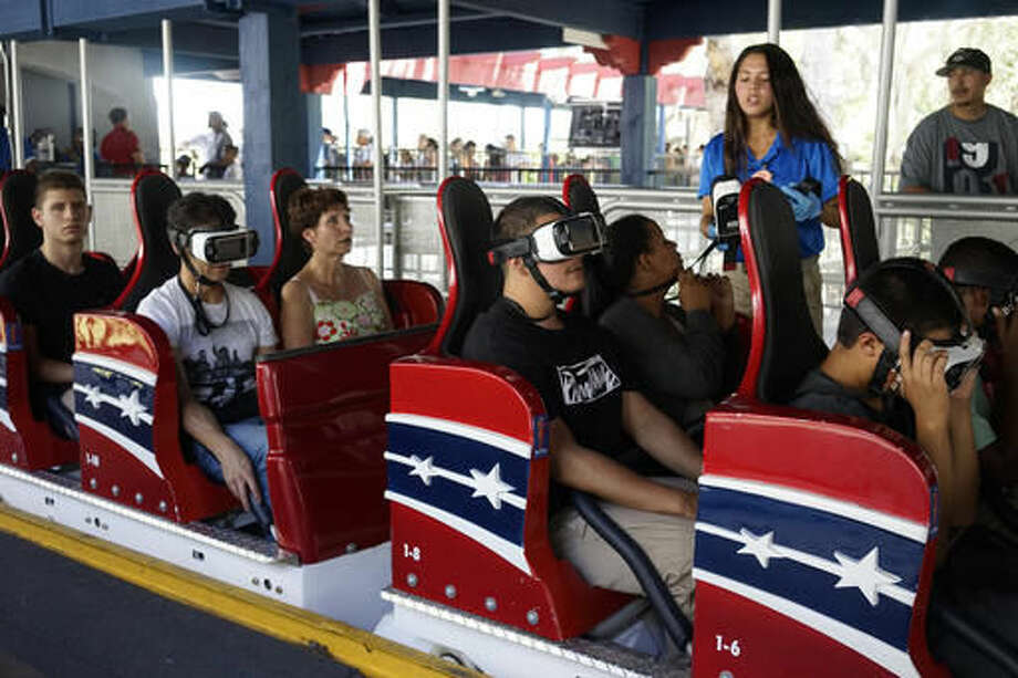 In this June 27, 2016 photo, riders put on headsets that give them a 360 degree view of an animation synched with the coaster's movements at The New Revolution, a virtual reality roller coaster at Six Flags Magic Mountain in Valencia, Calif. People who are curious about virtual reality but don't want to plunk down $1,000 or more on hardware are increasingly getting the chance to test out the medium for a price. From roller coaster rides to baseball games, VR can bring a new level of reality or simply detract from it. (AP Photo/Christine Armario)