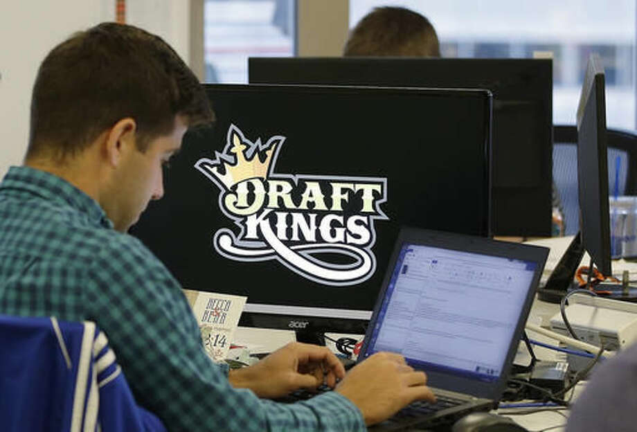 FILE - In this Sept. 9, 2015, file photo, Bear Duker, a marketing manager for strategic partnerships at DraftKings, works at his computer at the company headquarters in Boston. Daily fantasy sports rivals DraftKings and FanDuel have agreed to merge after months of speculation and increasing regulatory scrutiny. The two companies made the announcement Friday, Nov. 18, 2016, saying the combined organization would be able to reduce costs as they work to become profitable and battle with regulators across the country to remain legal. (AP Photo/Stephan Savoia, File)