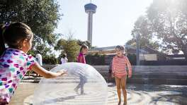 "(Center) Sofia Haynes, 9, plays in the ""Splash Pad"" at the opening ceremony of Yanaguana Garden Saturday Oct. 3, 2015 at Hemisfair Park. Yanaguana Garden is the first of three phases in Hemisfair's relaunch expected to open in the next few years."
