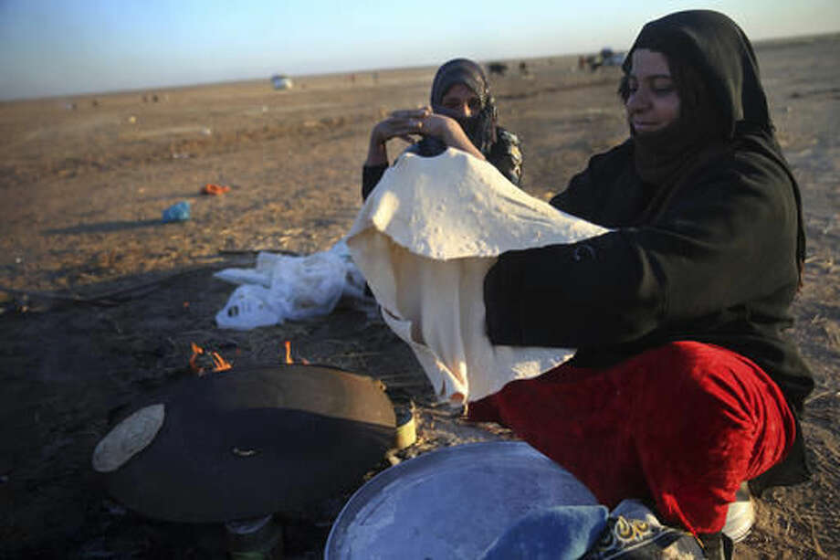 An Iraqi woman who fled with her family the fighting between Iraqi forces and Islamic State militants, makes bread as she waits to cross to the Kurdish controlled area, in an open field in the Nineveh plain, northeast of Mosul, Iraq, Friday, Nov. 18, 2016. Iraqi troops advanced cautiously into eastern districts of Mosul on Friday, facing stiff resistance from Islamic State militants a day after they paused their assault due to poor visibility, officers said. The pause also allowed the residents running out of food in areas liberated from IS to get some supplies from Iraqi troops and aid organizations. (AP Photo/Hussein Malla)